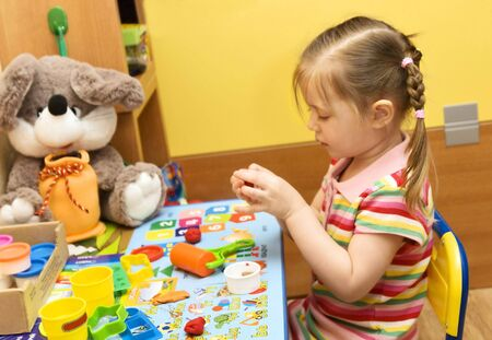 three year old girl playing with plasticine in her room