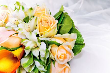 colorful wedding bouquet of fresh flowers against white dress background
