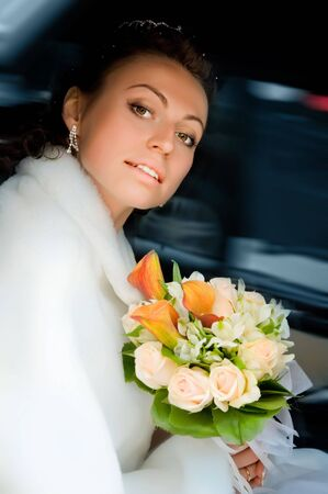 beautiful yong bride with her wedding bouquet sitting in a car photo