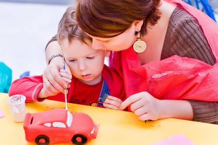mother and a 4-year old son painting together a toy car