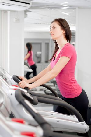 young beautiful woman making physical exercises on a running simulator