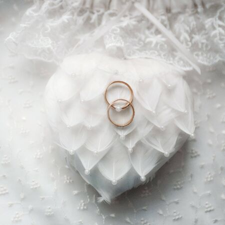 two gold wedding rings on a heart made of feathers Stock Photo