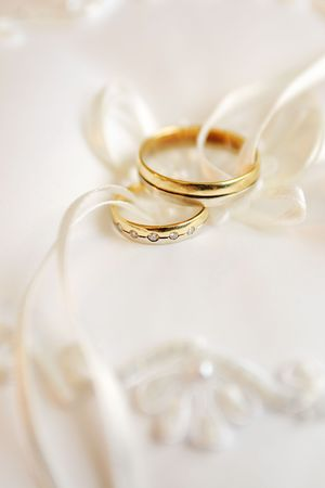 two gold wedding rings on a pillow photo