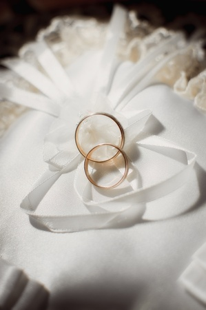 pair of gold wedding rings on a white wedding pillow Stock Photo - 9470574