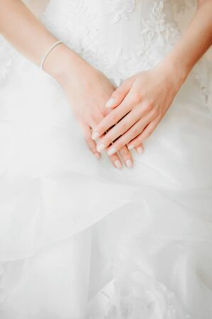 closeup of a brides hands upon white wedding dress