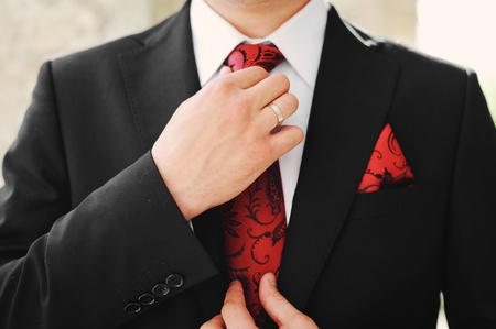 suit tie: elegant black grooms suit close up with red accents Stock Photo