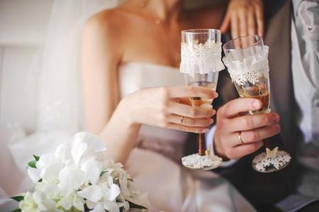 신부와 샴페인 아름답게 장식 된 웨딩 유리 잔을 들고 신랑