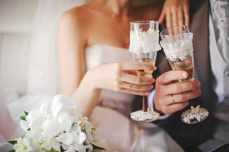 wedding party: bride and groom holding beautifully decorated wedding glasses with champaign
