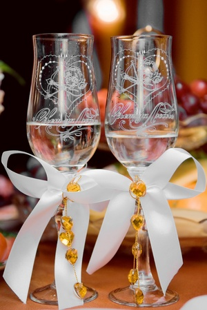 two beautifully decorated wedding glasses with champaign