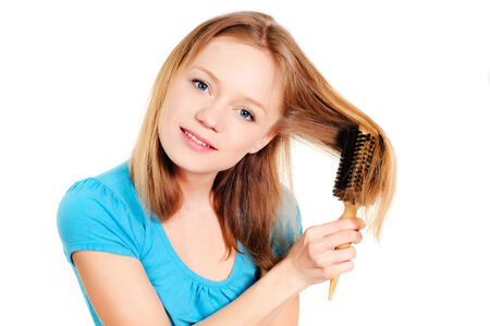 pretty young blond woman brushing her hair Stock Photo