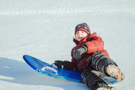 sledging: 9-year-old boy divertirsi slittino Archivio Fotografico