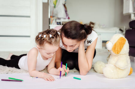 mother and little daughter having fun painting pictures Stock Photo