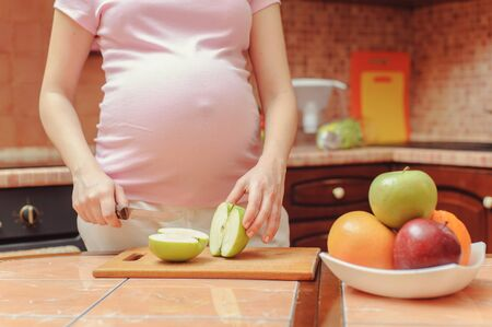 young pregnant woman cutting apples for fruit salad