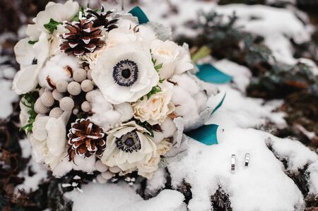 beautiful white and brown winter wedding bouquet and rings in snow