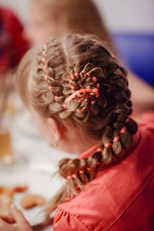 close up of a young girls haircut with pink ribbons