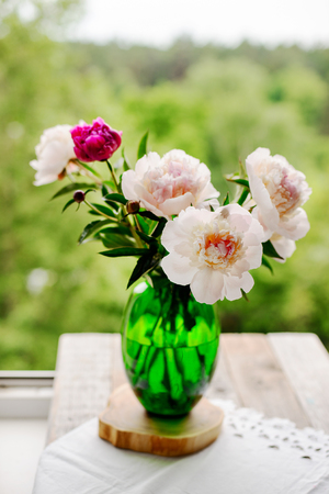 fresh and beautiful pink peonies in a green vase
