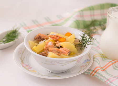 colorful and tasty homemade salmon and potatoes soup on white background Stock Photo
