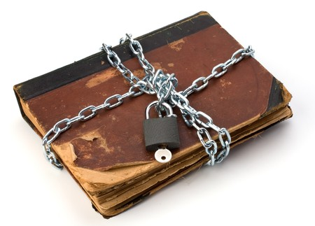 tattered book  ith chain and padlock isolated on white background photo