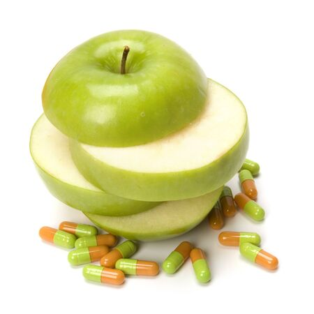 sliced apple and pills isolated on white background photo