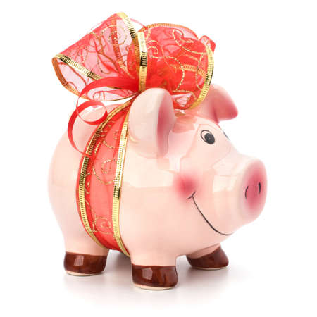 piggy bank money: Christmas deposit concept. Piggy bank with festive bow isolated on white. Stock Photo