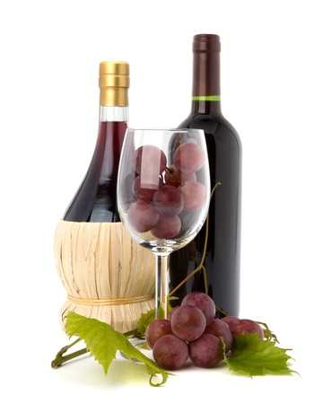 wine glass full with grapes and two wine bottles  isolated on white background photo