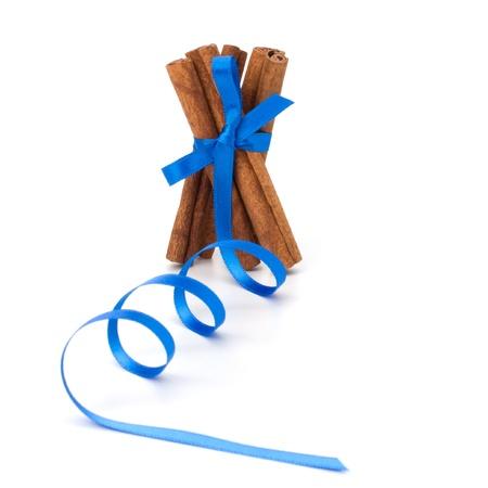 Festive wrapped cinnamon sticks isolated on white background photo