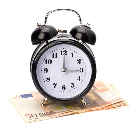 Money accumulation concept. Money and alarm clock isolated on white background. Stock Photo - 9054338