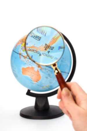 Japan map. Hand holding magnifying glass over earth globe Japan territory. photo