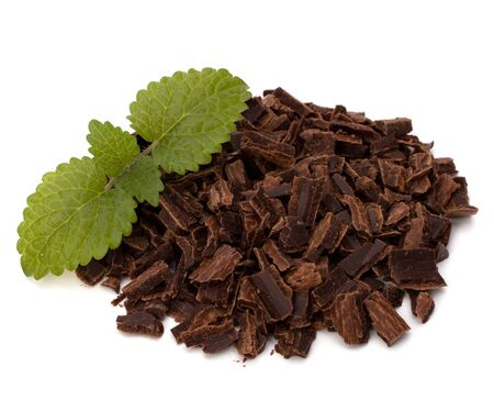 Crushed chocolate shavings pile and mint leaf isolated on white background photo