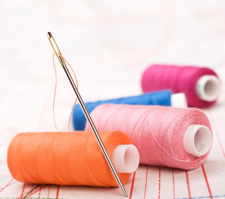 Spool of thread and needle. Sew accessories on blurred background. photo
