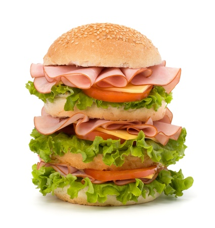 junk: Big appetizing fast food sandwich with lettuce, tomato, smoked ham and cheese isolated on white background. Junk food hamburger. Stock Photo