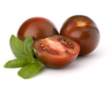 Tomato kumato and basil leaf isolated on white background photo