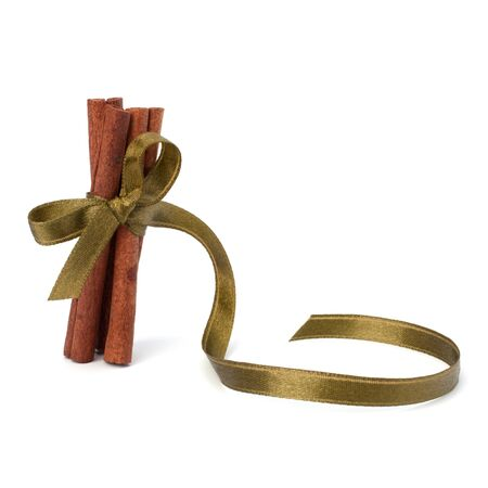 Festive wrapped cinnamon sticks isolated on white background photo