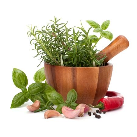 mortero: hierbas frescas y especias aromatizantes en mortero de madera aisladas sobre fondo blanco