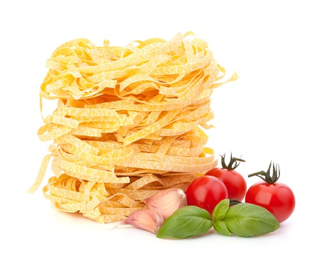 Italian pasta tagliatelle nest and cherry tomato isolated on white background photo