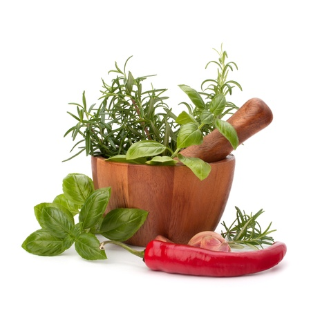 fresh flavoring herbs and spices in wooden mortar isolated on white background