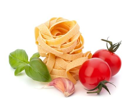 comida gourment: Nido de tallarines de pasta italiana y el tomate cereza aisladas sobre fondo blanco