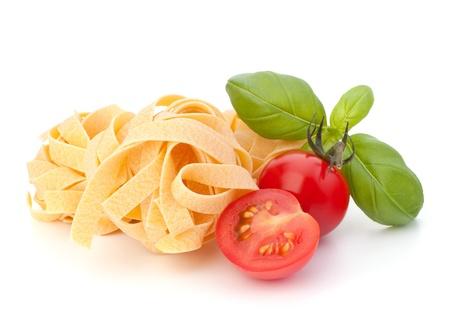 Nido de tallarines de pasta italiana y el tomate cereza aisladas sobre fondo blanco