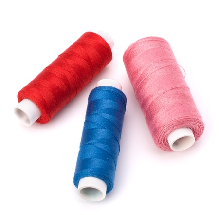 Colourful spools of thread isolated on white background photo