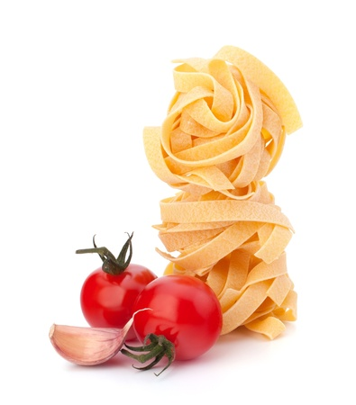 Italian pasta fettuccine nest  and cherry tomato isolated on white background photo