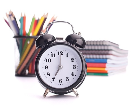 Alarm clock, notebook stack and pencils. Schoolchild and student studies accessories. Back to school concept. Stock Photo - 14313675