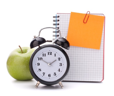 Alarm clock, blank notebook sheet and apple. Schoolchild and student studies accessories. Back to school concept. photo