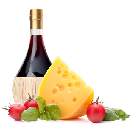Red wine bottle, cheese and basil leave still life isolated on white background cutout. Italian food concept. photo