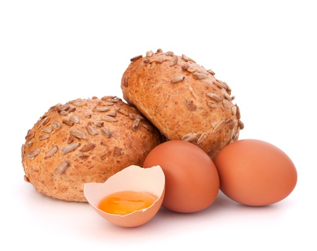 Bun with seeds and broken egg isolated on white background photo