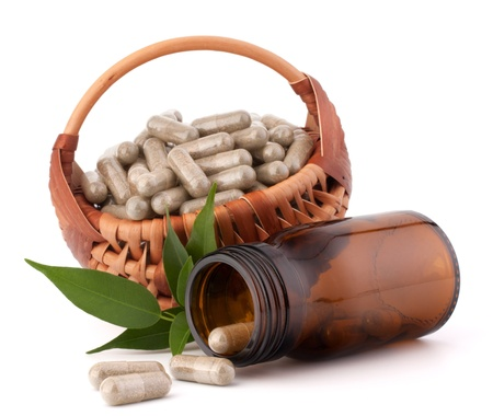 Herbal drug capsules in wicker basket isolated on white background cutout. Alternative medicine concept. Stock Photo