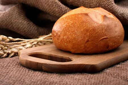 Loaf of bread and wheat ears still life on rustic background photo