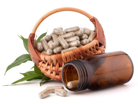 eastern health treatment: Herbal drug capsules in wicker basket isolated on white background cutout. Alternative medicine concept. Stock Photo