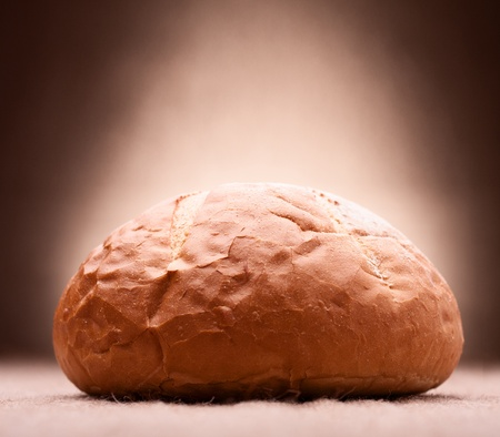 Loaf of wheat bread on rustic background photo