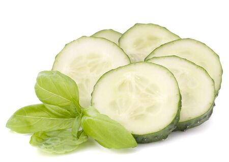 Sliced cucumber vegetable and basil leaves still life isolated on white background cutout photo