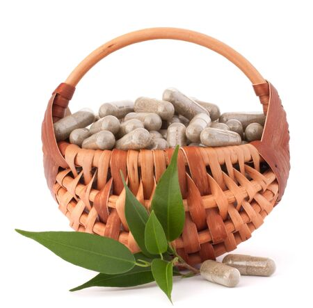 Herbal drug capsules in wicker basket isolated on white background cutout. Alternative medicine concept. Stock Photo - 18504619